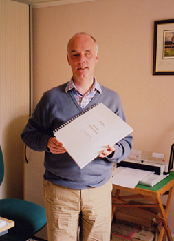 A photograph of Roger Firman holding a bound Golden Chord transcription